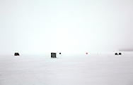 Ice fishing shack and fisherman walking through the frozen fog on Lake Mendota in Madison, Wisconsin.