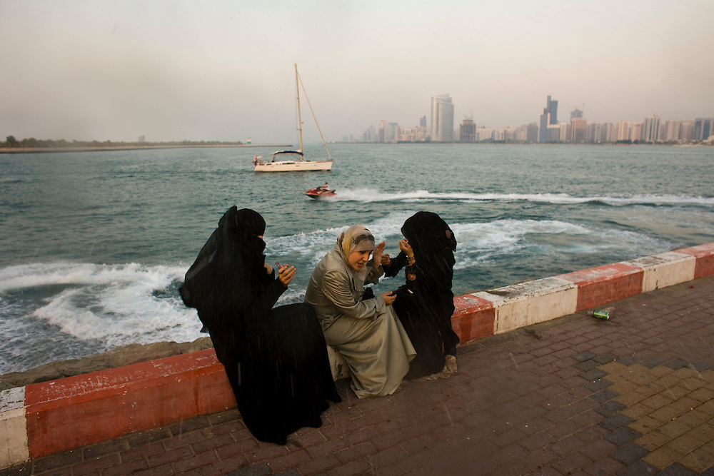 Young  women cower form water being sprayed on them by boys on jet skis Abudhabi skyline lit by the setting sun,