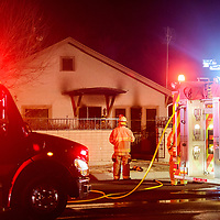 Gallup firefighters work outside a house fire on Maloney Avenue in Gallup Monday.