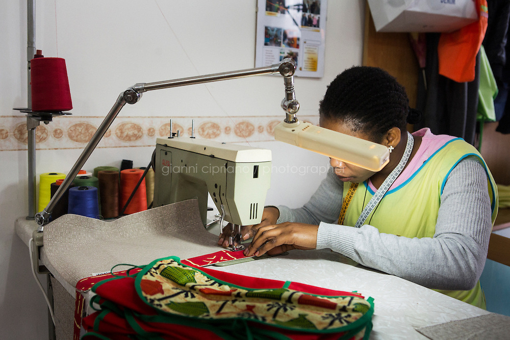 CASERTA, ITALY - 25 FEBRUARY 2015: A Nigerian immigrant woman and ex-sex worker sews fabrics for an arm chair caddy at the New Hope tailor's shop in Caserta, Italy, on February 25th 2015.<br /> <br /> New Hope is an ethnic tailor's shop that makes a variety of colourful products working mainly african fabrics. The New Hope social cooperative, founded in 2014, promotes a training workshop for your immigrant women, many of which have children, that want to integrate in Italian society.