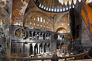 High angle view of interior showing Islamic elements from the balcony of the tribune, Hagia Sophia, 532-37, by Isidore of Miletus and Anthemius of Tralles, Istanbul, Turkey. Hagia Sophia, The Church of the Holy Wisdom, has been a  Byzantine church and an Ottoman mosque and is now a museum. The current building, the third on the site, commissioned by Emperor Justinian I, is a very fine example of Byzantine architecture. The historical areas of the city were declared a UNESCO World Heritage Site in 1985. Picture by Manuel Cohen.