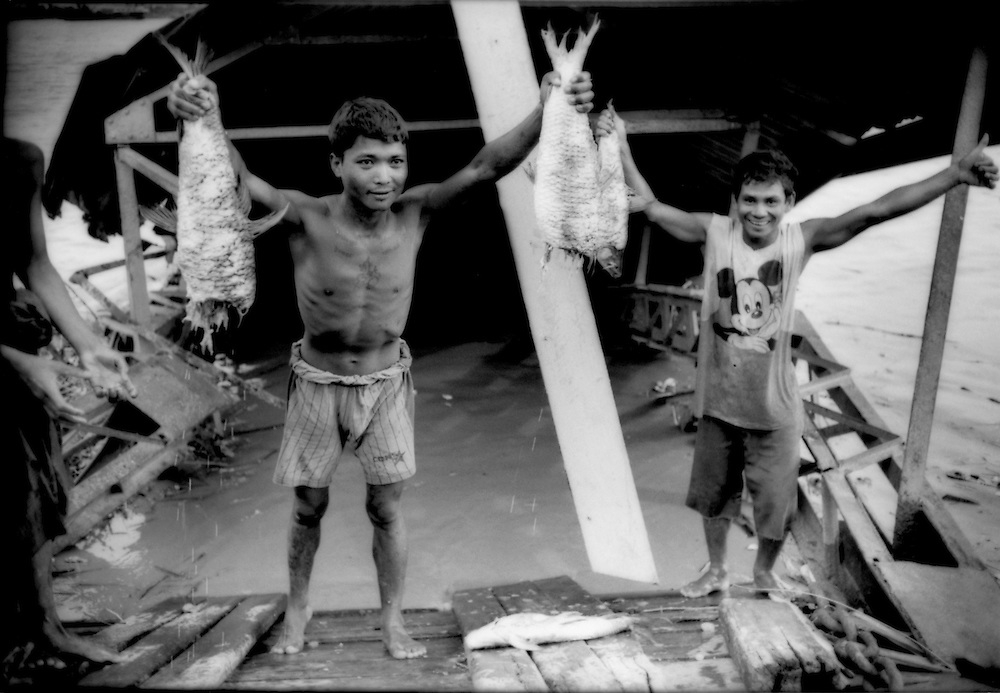 Intoxicated and hungry men stand holding rotting fish that they plucked from the Yangon River and plan to eat in front of a battered passenger ferry dock that was destroyed in Cyclone Nargis, Burma (Myanmar).