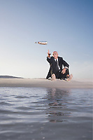 Business man sitting on beach throwing message in bottle into sea low angle view