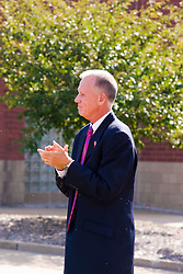 19 September 2009: Doug Collins clap with satisfaction as he looks at the newly unveiled statue even while being hassled by a large gathering of gnats.  Illinois State University took the day to celebrate 2 of it's own, the late Will Robinson and national hero Doug Collins.  Will Robinson became the first black head basketball coach in NCAA Division I history when names ISU basketball coach in 1970.  Doug Collins was an Illinois State standout basketball player who represented the United States in the 1972 Olympics, played NBA ball for several years where he later coached and recently recieved the Curt Gowdy Media Award for career in broadcasting.  A statue was erected in their honor on the terrace just north of the main entrance to Redbird Arena on ISU's campus in Normal IL