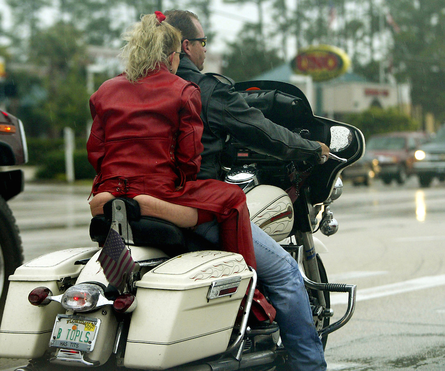 "A woman in a thong and leather chaps rides down the road on a Harley sporting a ""B TopLS"" license plate at Bike Week in Daytona Beach, Florida March 7, 2005.  The ten-day event attracts motorcyclists of all varieties with over 500,000 expected this year."