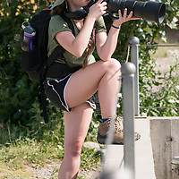 A student photographs with a long lens. National Geographic Student Expeditions high school students photograph at the Montana Grizzly Encounter facility on the 4th of July during the 2017 Yellowstone Photo Workshop. Bozeman, Montana.
