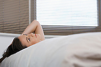 Young woman lying in bed looking up