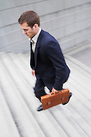 Business man carrying briefcase ascending steps elevated view