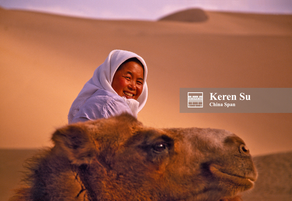 China, Silk Road, Gansu Province, Dunhuang, woman with camel in the desert