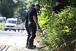 © Licensed to London News Pictures. 29/08/2016. Leeds, UK. Police teams in gloves search around what is believed to be the scene of shooting that took place last night. This is as yet unconfirmed by the police. The incident happened in the Chappeltown area of Leeds where the West Indian Carnival is taking place this weekend. Photo credit : Ian Hinchliffe/LNP