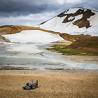 Hiker taking a break, reading a book. Hveradalir Geothermal Valley in Kerlingarfjöll Mountain Range, Interior of Iceland.
