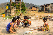 "01 MARCH 2014 - MAE SOT, TAK, THAILAND: Children play on the ground in front of their home in a small Burmese community in the forest a few kilometers north of Mae Sot. Mae Sot, on the Thai-Myanmer (Burma) border, has a very large population of Burmese migrants. Some are refugees who left Myanmar to escape civil unrest and political persecution, others are ""economic refugees"" who came to Thailand looking for work and better opportunities.    PHOTO BY JACK KURTZ"