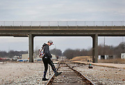 """Mirenda Barrows crosses over some train tracks while walking to the Gathering Tree to hang out with some of what she calls her """"residentially challenged"""" friends on Thursday, Feb. 15, 2018. Mirenda was pregnant when she was hit by a truck while crossing the street in June 2017. She suffered extensive injuries and lost her baby."""