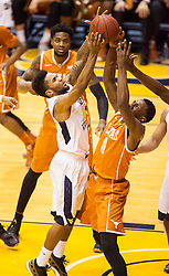 Jan 20, 2016; Morgantown, WV, USA; West Virginia Mountaineers guard Tarik Phillip (12) grabs a rebound over Texas Longhorns guard Tevin Mack (0) during the first half at the WVU Coliseum. Mandatory Credit: Ben Queen-USA TODAY Sports