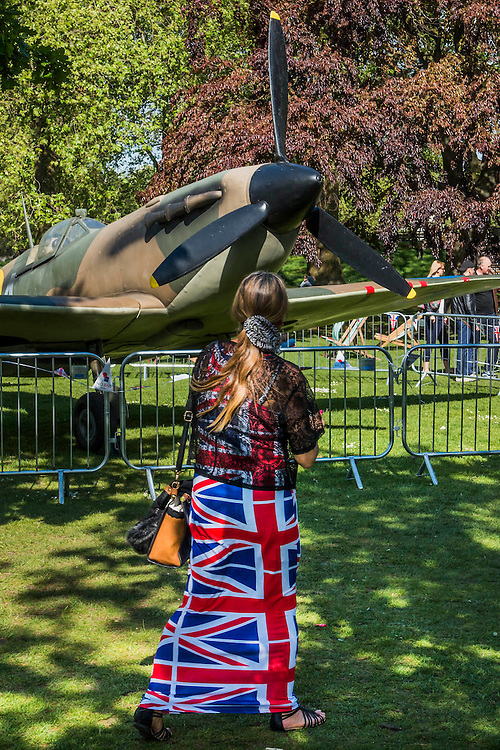 A Spitfire and a woman in a patriotic outfit in St James Park. VE Day 70 commemorations - Three days of events in London and across the UK marking historic anniversary of end of the Second World War in Europe. Trafalgar Square, scene of jubilant celebrations marking the end of the Second World War in Europe on 8 May 1945, plays a central part in a host of national events, which include a Service of Remembrance at the Cenotaph, a concert in Horse Guards Parade, a Service of Thanksgiving at Westminster Abbey, a parade of Service personnel and veterans and a flypast.