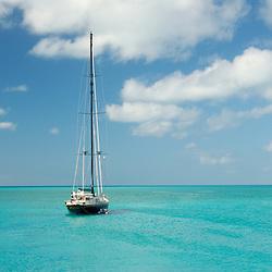 "Sailing yacht ""Tenacious"" motoring slowly through the shallow turquoise waters off of Samson Cay, Bahamas."