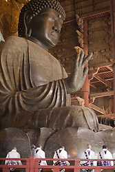 Asia, Japan, Honshu island, Nara, monks under giant bronze Buddha in the Great Buddha Hall (Daibutsuden), within the Todaiji Temple complex.  Constructed in 752 and rebuilt in 1692, it is the largest wooden building in the world and a U.N. World Heritage Site