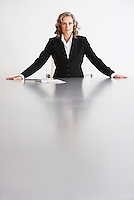 Female Business Executive Sitting by table arms outstretched