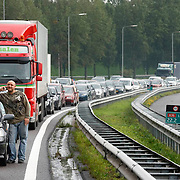 Nederland Rotterdam 30-09-2010 20100930..File op de rijksweg A16 op de oosterlijke ring, lange rijen met auto's staan stil. Man is uit auto gestapt om en rookt een sigaret en belt met zijn mobiel. Handsfree bellen, telefoneren, mobieltje, handen vrij, gsm, communicatie, communiceren.  Traffic jam. Holland, The Netherlands, dutch, Pays Bas, Europe ..Foto: David Rozing