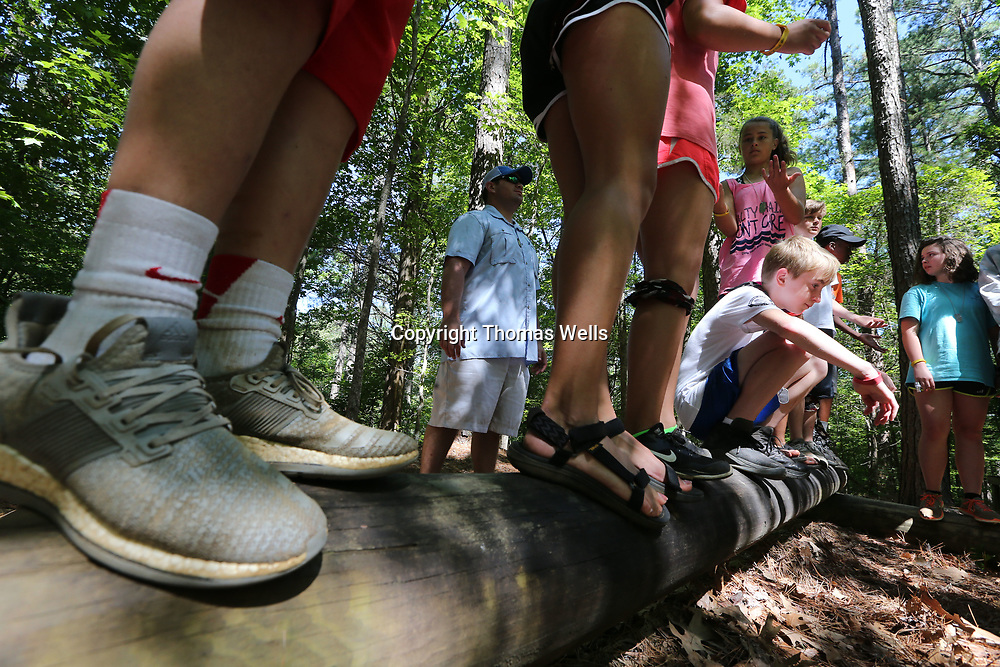 Cameron Christian, 12, of Tupelo kneels down so his teammates can move pass while trying to line up in order of their shoe size without falling off the log or speaking as part of a team building activity.