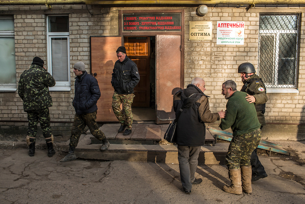 ARTEMIVSK, UKRAINE - FEBRUARY 8, 2015: An ambulance driver named Tariel, second from right, a Ukrainian Army medic, arrives at a hospital for treatment for a shrapnel wound to the arm received during shelling near a medical treatment point for Ukrainian fighters in Artemivsk, Ukraine. Fighting between pro-Russia rebels and Ukrainian forces there over the past two weeks has dealt steady casualties to Ukrainian fighters and civilians. CREDIT: Brendan Hoffman for The New York Times