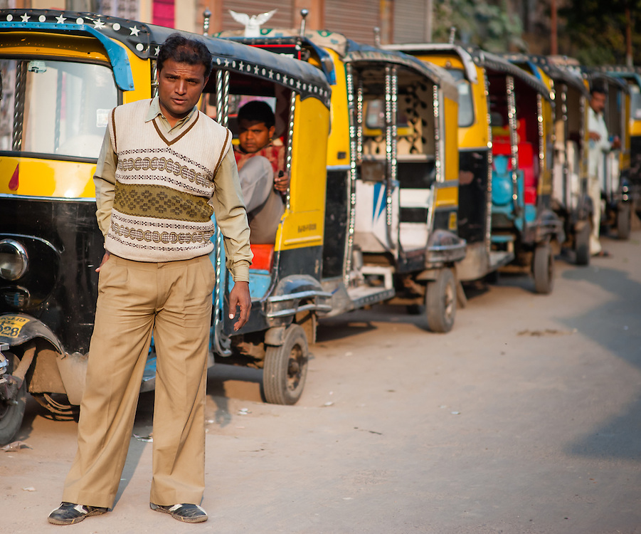Autorickshaw driver waiting for customers at taxi stop (India)