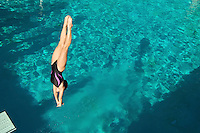 Female diver diving into pool mid air
