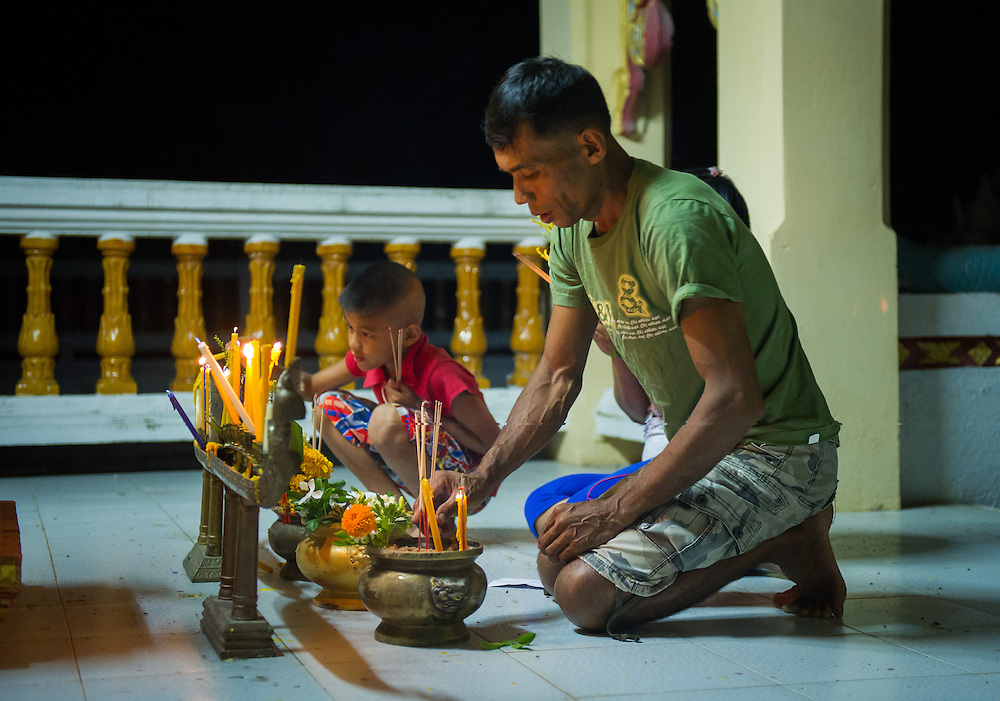 A family lights prayer candles and incense during Visakha Puja Day celebrations in rural Nakhon Nayok, Thailand. PHOTO BY LEE CRAKER