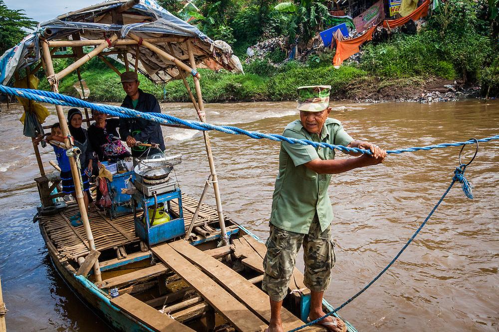 Pak Among (70) crosses passengers across the Citarum River.  He receives 5 cents per person. Sukamaju Village, Majalaya.  ..Credit: Andri Tambunan for Greenpeace