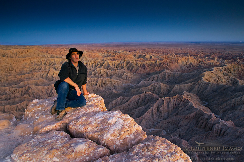 Tourist enjoying a quiet evening overlooking eroded hills of the Borrego Badlands, Fonts Point, Anza Borrego Desert State Park, San Diego County, California