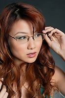 Beautiful Chinese woman wearing glasses over colored background