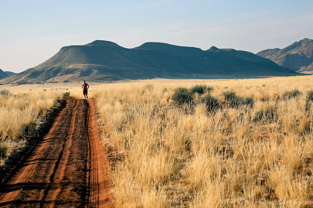 Africa, Namibia, Sossussvlei. One man runs on an endless stretch of road through the NamibRand Nature Reserve.