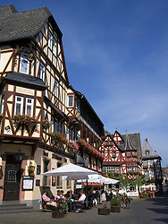 Street cafe beside historic buildings in historic town of Bacharach on River Rhine in Rhineland Germany