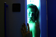Tanning Booth. Ultraviolet (UV) rays from the lights cause a suntan to develop by stimulating pigment production in her skin. Sunbooths use longer wavelength UVa rays to reduce the risk of sunburn and skin cancer. The pigment produced, melanin, protects the skin from overexposure to UV radiation.