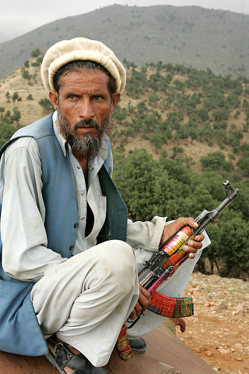 20th August 2007.Tora Bora.A local man armed with a Kalashnikov acts as a body guard for a Tribal leader making a visit to Tora Bora on the 20th August 2007. Tora Bora was one of the mountain hideouts of Osama Bin Laden and the Al-Qaeda fighters. It was destroyed during the battle of Tora Bora at the beginning of this recent conflict.  In the past weeks it has been the scene of a joint US and Afghan offensive against Taliban fighters who have moved back into the area...