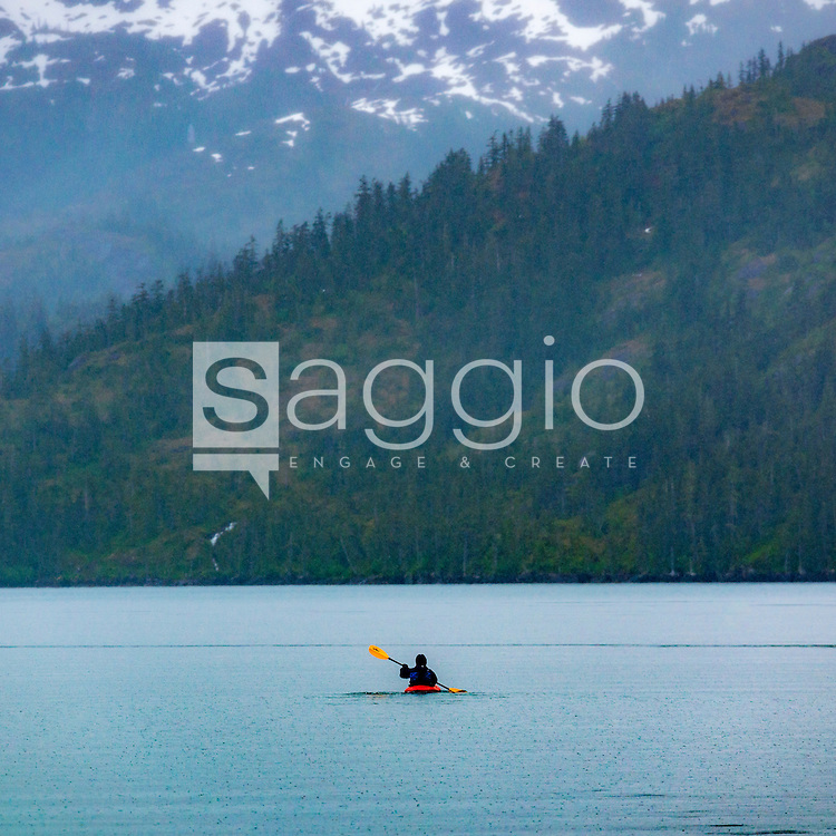 A lone sea kayaker paddles along the coast in Prince William Sound, Alaska.
