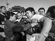 "07 MARCH 2015 - NAKHON CHAI SI, NAKHON PATHOM, THAILAND: Volunteers bring a man out of a trance state at the Wat Bang Phra tattoo festival. Wat Bang Phra is the best known ""Sak Yant"" tattoo temple in Thailand. It's located in Nakhon Pathom province, about 40 miles from Bangkok. The tattoos are given with hollow stainless steel needles and are thought to possess magical powers of protection. The tattoos, which are given by Buddhist monks, are popular with soldiers, policeman and gangsters, people who generally live in harm's way. The tattoo must be activated to remain powerful and the annual Wai Khru Ceremony (tattoo festival) at the temple draws thousands of devotees who come to the temple to activate or renew the tattoos. People go into trance like states and then assume the personality of their tattoo, so people with tiger tattoos assume the personality of a tiger, people with monkey tattoos take on the personality of a monkey and so on. In recent years the tattoo festival has become popular with tourists who make the trip to Nakorn Pathom province to see a side of ""exotic"" Thailand.   PHOTO BY JACK KURTZ"