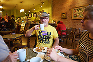 A man with an anti-suicide message on his teeshirt raises a cup og coffee at a table with two other people in Coffee Exchange in 2019 in Windsor, Ontario.