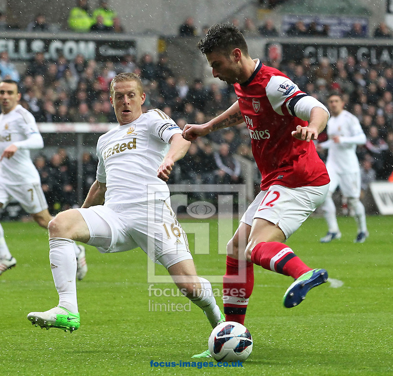 Picture by Mike  Griffiths/Focus Images Ltd +44 7766 223933.16/03/2013.Garry Monk of Swansea City attempts to stop Olivier Giroud of Arsenal from shooting during the Barclays Premier League match at the Liberty Stadium, Swansea.