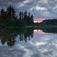 landscape consisting of a lake, trees and cloudy sunset reflected on the lake surface.