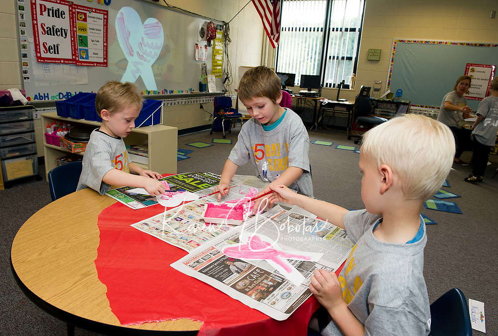 Adrian, Isaac and Desmond paint pink hearts for decorations to be used during the annual Breast Cancer Walk coming up in Laconia at Pleasant Street School Thursday morning for their Day of Caring with the United Way.  (Karen Bobotas/for the Laconia Daily Sun)