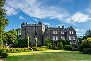 Comlongon Castle is a restored Medieval Scottish tower house dating from the late 1400s. Guests can stay in the attached Edwardian hotel, a baronial style mansion built 1900-02, set in 120 acres of manicured gardens, sweeping lawns, carp pond, lakes and woodlands, near Clarencefield and Dumfries, in southwest Scotland, United Kingdom, Europe. Originally built by the Murrays of Cockpool, Comlongon Castle remained in the Murray family until 1984. The castle is 50 feet square and stands 70 feet high, with walls over 4 meters thick, with impressive displays of weapons, armor and banners.