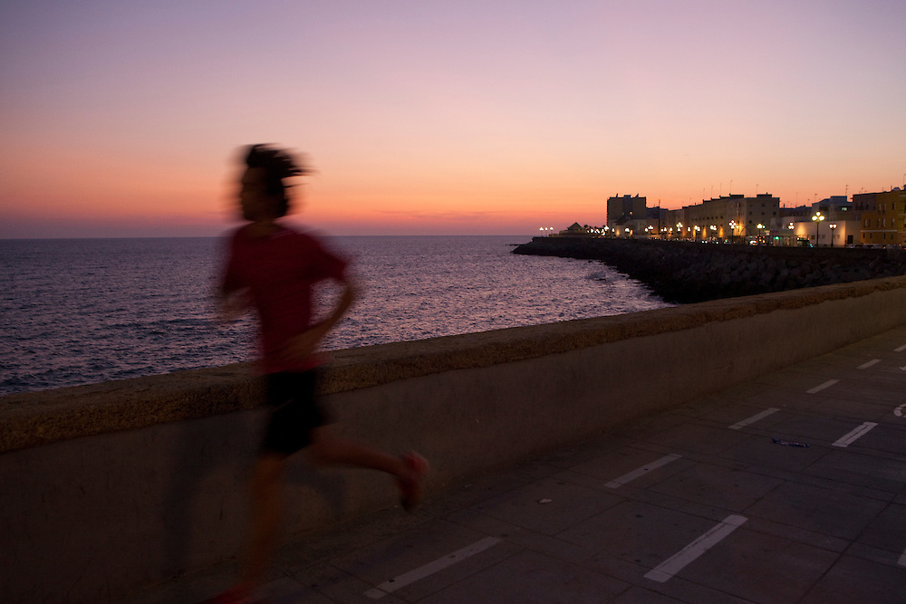 A young man jogging at sunset on on Campo del Sur, Cadiz, Andalucía, Spain.