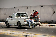 During a fierce firefight on Al Jala'a avenue, rebels Libyan push their attack on Gadhafi's headquarters in Bab Al Azizyia in Tripoli. A rebel vehicle loaded with wounded fighters hastily backs up as rebels force their way toward one of the fortified compound main gate. 23 August 2011.