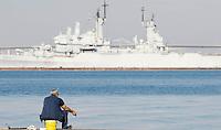 Un pescatore sul porticcolo, a Taranto. Sullo sfondo, una nave militare