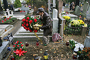Lodz, Poland, cemetery on All Saints Day. Man whose wife died earlier in the year decorates her grave.