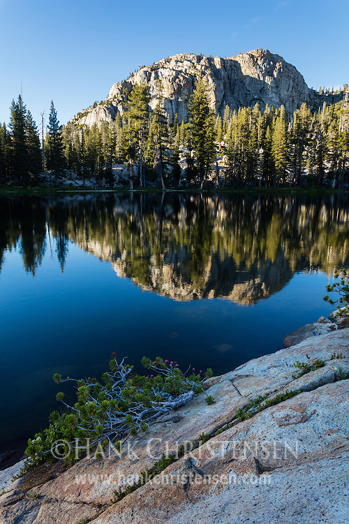 Cliffs to the north of Gem Lake reflect in the still water at sunset, Emigrant Wilderness, CA.