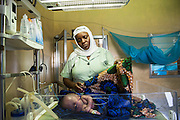 Sophia a medical attendant caring for a very sick baby who has just been delivered by cesarian section, NICU (Neonatal Intensive Care Unit) ward. St Walburg's Hospital, Nyangao. Lindi Region, Tanzania.