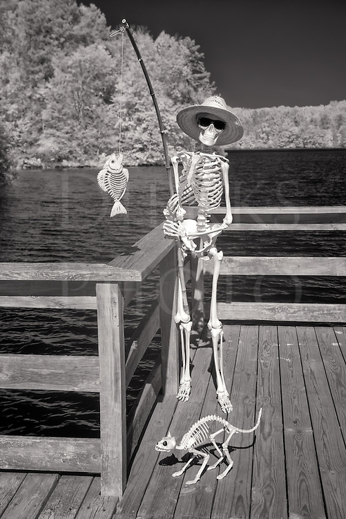 Here&rsquo;s a vacation shot of Jake&rsquo;s day at the lake fishing from the dock with a bamboo pole, a skeleton of sporting leisure wearing Ray-Bans and a straw hat. He&rsquo;s grinning and holding up his catch while a hungry and obviously underfed scavenging cat has his eye on the prize too. All in all, it was another good day outdoors in the afterlife.<br />