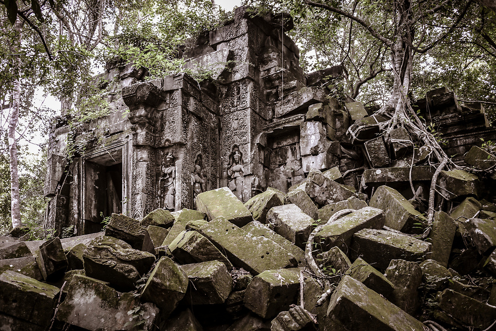 "Prasat Beng Mealea (Khmer: ប្រាសាទបឹងមាលា), meaning ""lotus pond"", is a Hindu temple built of sandstone to worship Vishnu during the Angkor Wat period (early 12th century). It is located 40 km east of the main group of temples at Angkor, Cambodia, on the ancient royal highway to Preah Khan Kompong Svay. The temple complex lies in ruins and overgrown by trees."